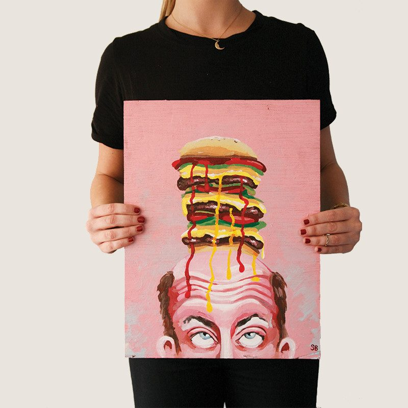 photograph of a woman holding an original painting of a man's face rolling his eyes up to see the massive burger he has on top of his head and the sauce leaking over his forehead by Wunderkid Sienne Brown called BurgerMan