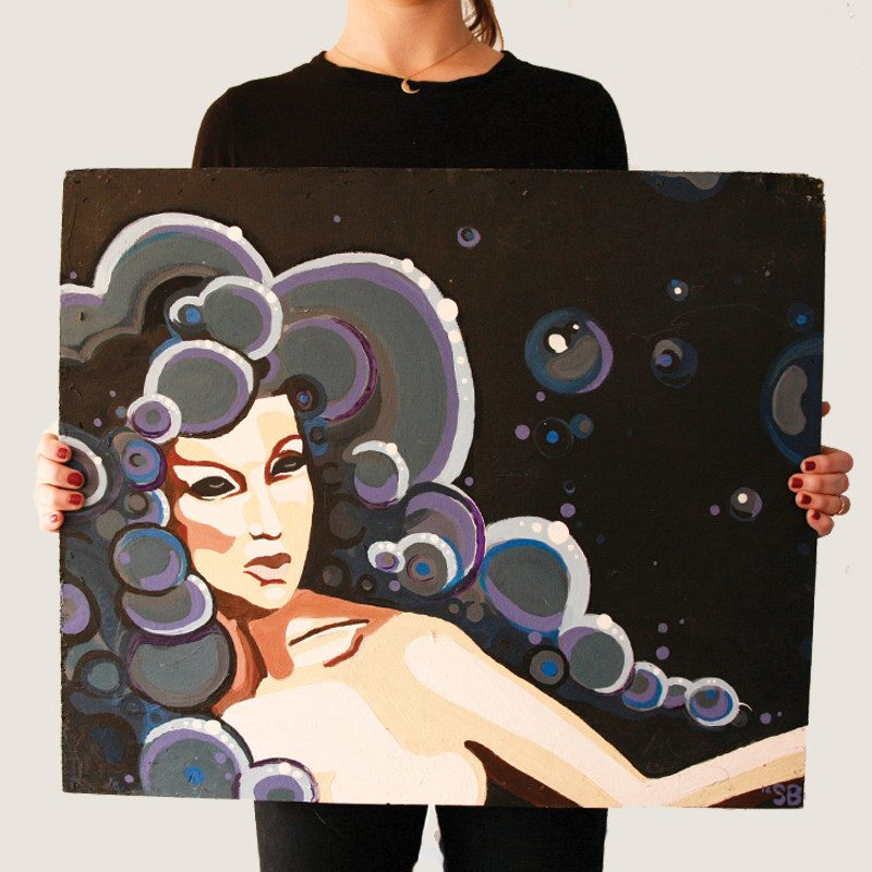 photograph of a woman holding an original abstract portrait painting of a woman with bubble hair in a black background called cloud lady by Sienna Brown