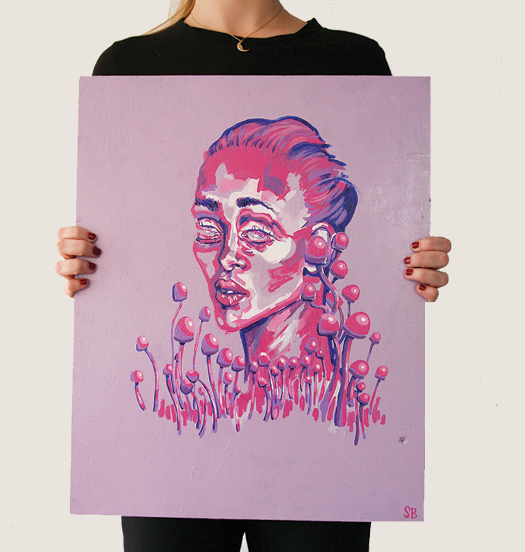 photograph of a woman holding an original magenta abstract portrait painting of a woman in the middle of a mushroom field called magenta dream by artist Sienna Brown