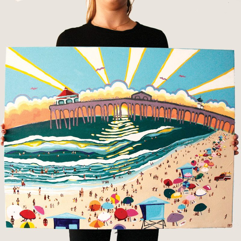 photograph of a woman holding an original painting of people enjoying a day at the beach with a beautiful sunset behind a pier called surf city by artist Sienna Brown