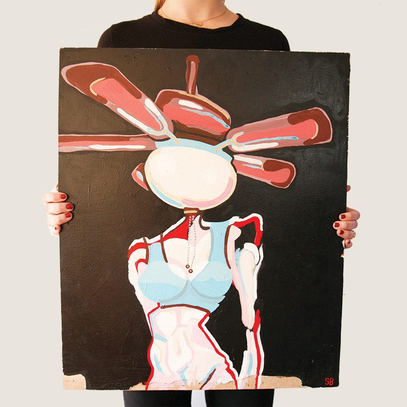 photograph of a woman holding an original abstract painting of a woman shaped body with propeller for head in a couple black colored background called windy by artist Sienna Brown