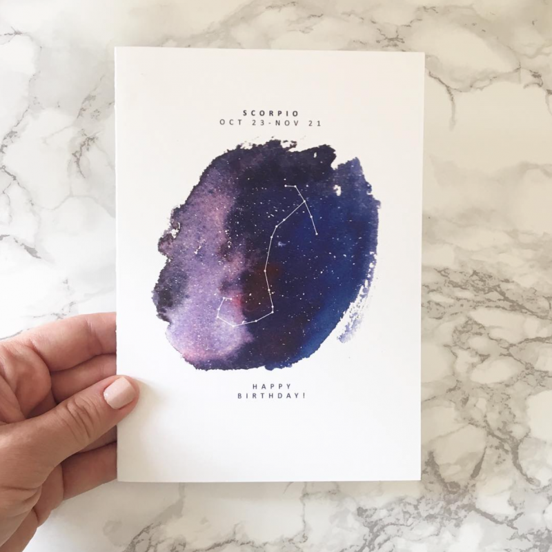 photograph of a woman holding a birthday greeting card with astrological sign for Scorpio people by artist Lauren Suh