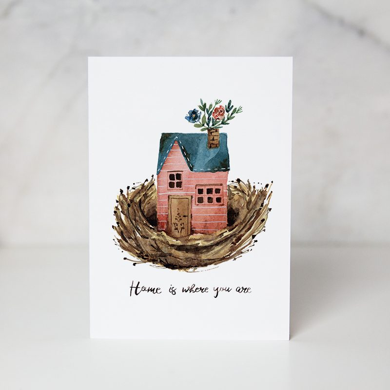 Greeting card with the wording home in where you are underneath the painting of a house in a nest and some flowers coming out from the chimney in a complete white background called home is where you are by artist Lucia De Marco
