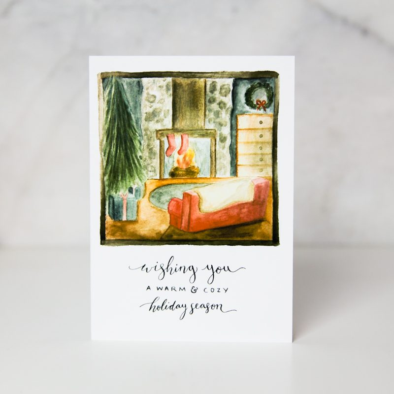 christmas card of a drawn cozy living room with a christmas tree, a fire place and a red couch with the Wishing you a warm and cozy holiday season underneath balled warm and cozy by artist Sarah Brown