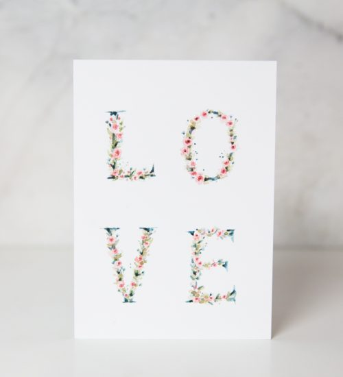 love card with LOVE written with with painted flowers in a complete white background calle L-O-V-E by artist Lucia De Marco