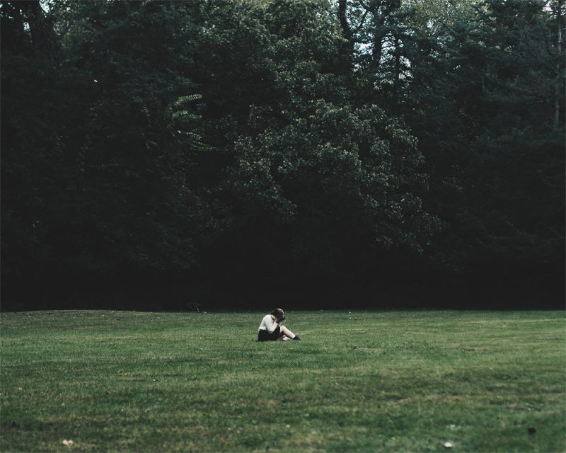 merry steed photography of a girl sitting in the middle of a field called lost