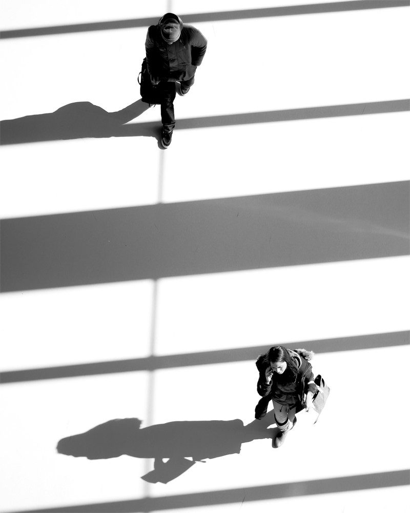 nicole raquinio photograph of two people walking with shadows called shadow play