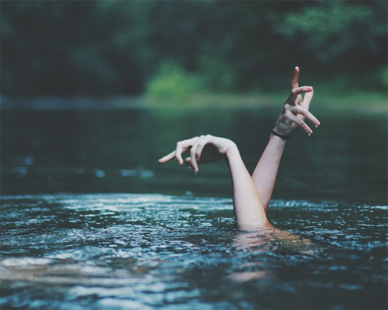 merry steed photography of a girl under water with hands called drowning