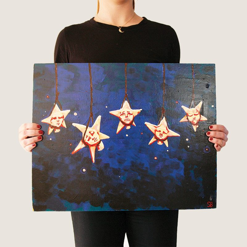 Photograph of a woman holding an original painting of five stars hanged with ropes from the sky in a dark blue background called hanging stars by artist Sienna Brown