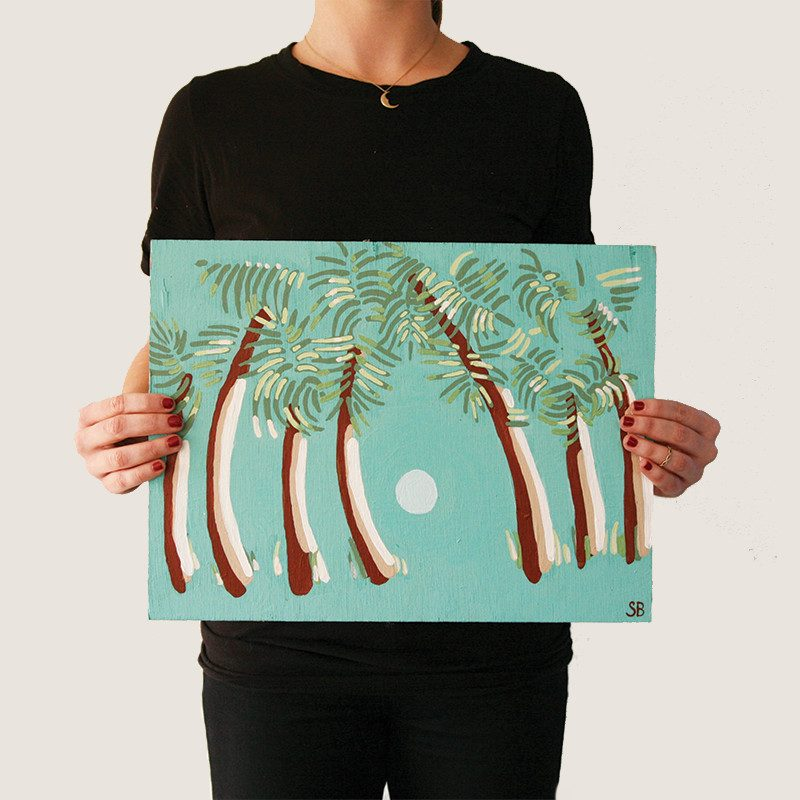 photograph of a woman holding an Original painting of a palm trees facing a sunset in a turquoise colored background called palms by artist Sienna Brown