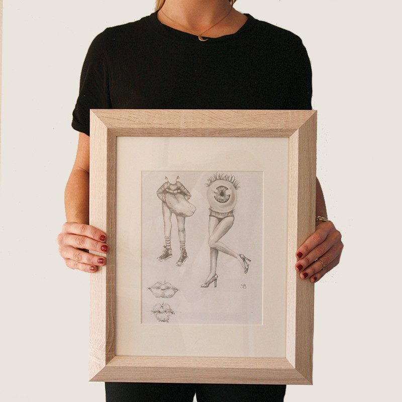 photograph of a woman holding an Original sketchbook drawing of a mouth and an eye with woman legs by artist Sienna Brown