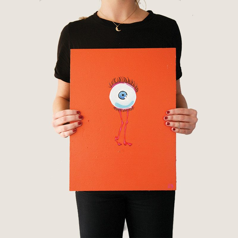 photograph of a woman holding an original abstract painting of a eye with long eye lashes and skinny pink legs in a complete flashy orange background called wink by artist Sienna Brown