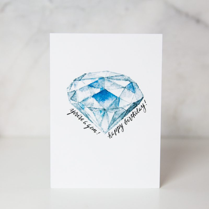 birthday greeting card with you are a gem. happy birthday! wording and a diamond colored gemstone painted in the middle in a white background called diamond birthday by artist Lauren Suh