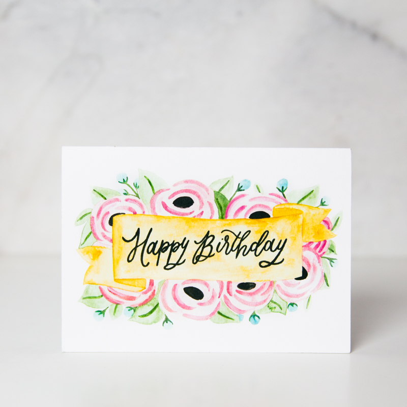 Birthday Greeting Card With Happy Wording Written On Painted Banner Pink Flowers Behind Called