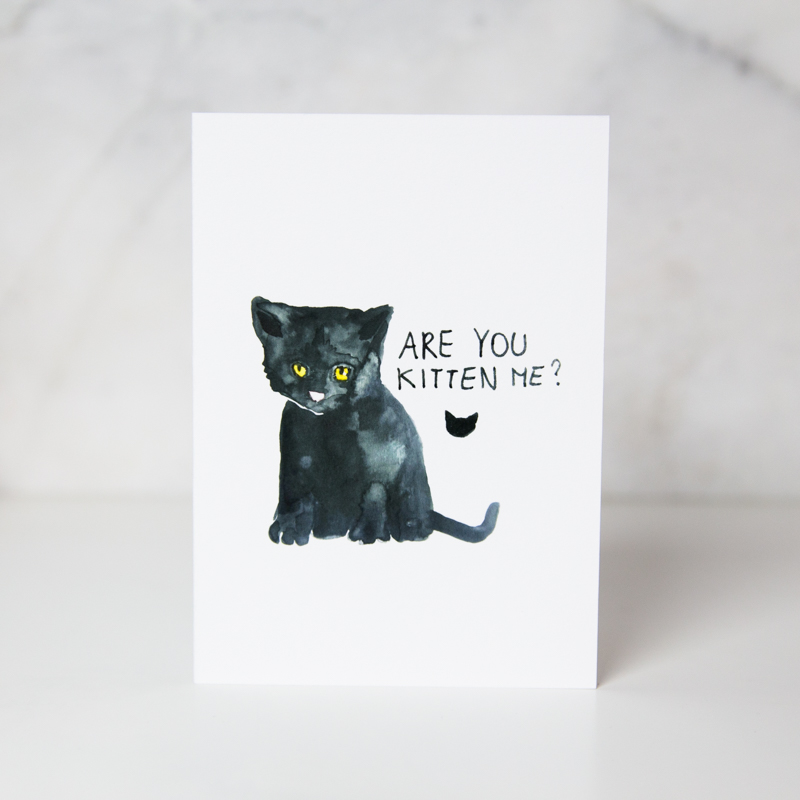 Sympathy greeting card of a drawn black cat with the Are you kitten me? wording next to it in a complete white background called are you kitten me by artist Ania Tomzynska
