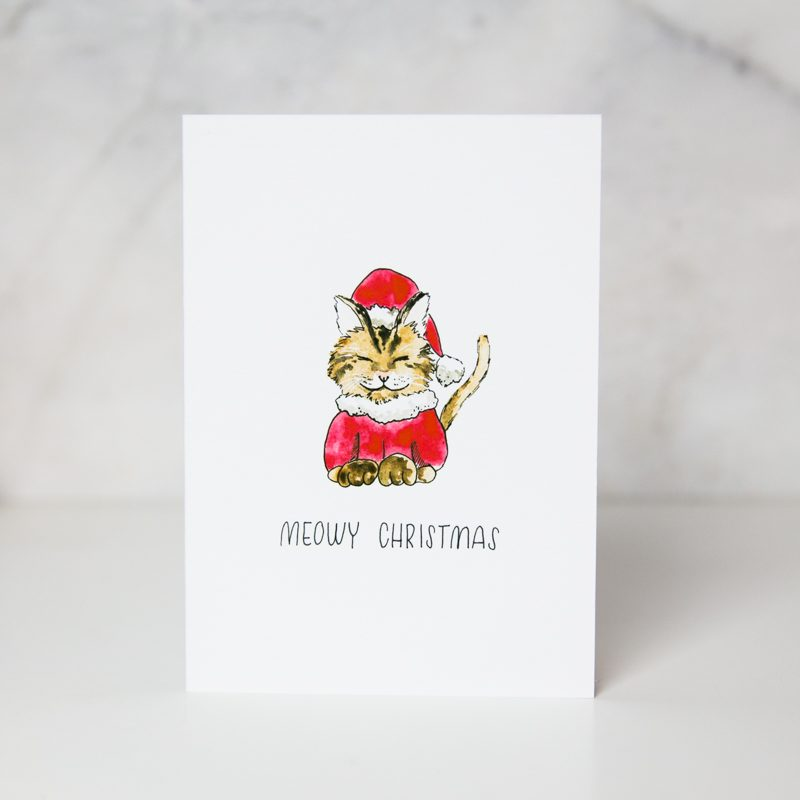 christmas greeting card of a drawn santa claus dressed up cat smiling with the the Meowy Christmas wording in a complete white background called meowy christmas by artist Theodora Nguyen