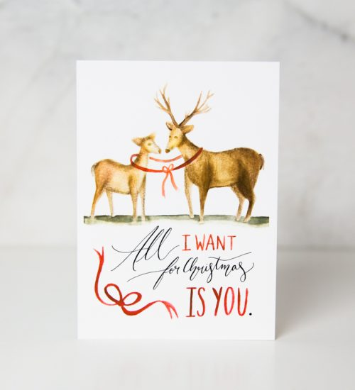 christmas card of two drawn deers tied up with with a red ribbon with the All I want for christmas is you wording underneath in a complete white background called all I want for Christmas is you by artist Sarah Brown