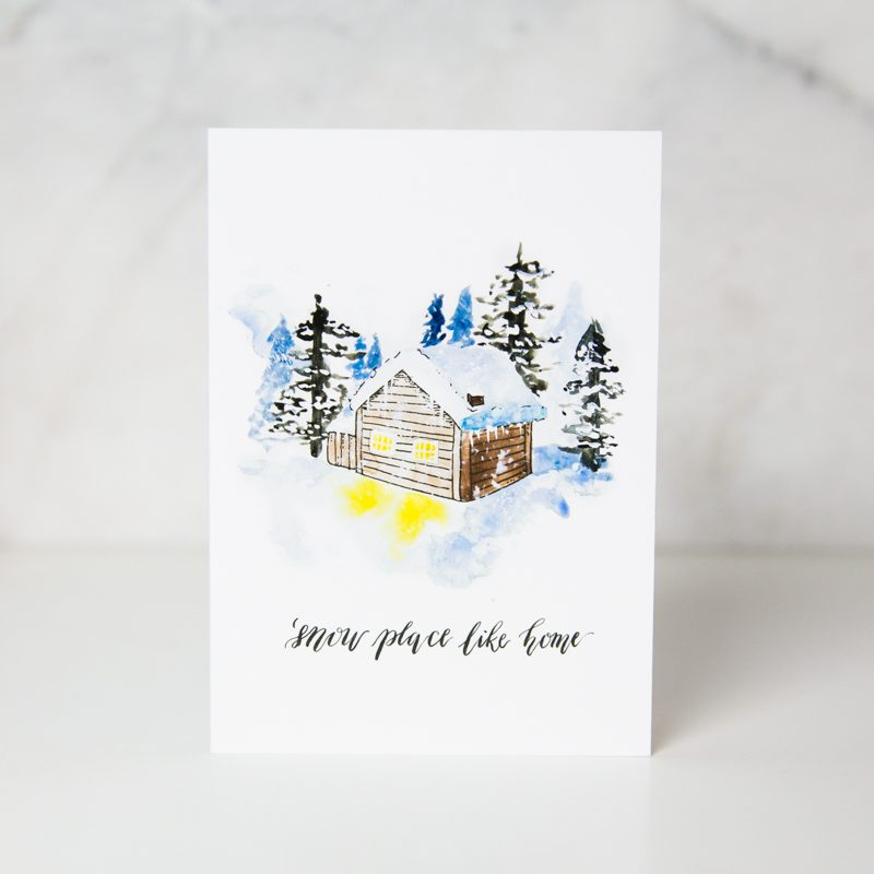 Christmas greeting card of a drawn snowed cabin surrounded by giant trees and snow called like snow place like home by artist Theodora Nguyen