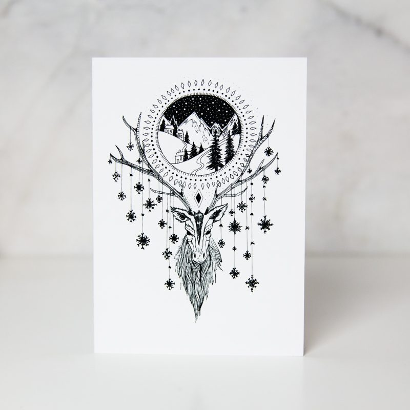 Christmas card of a winter scene above a drawn deer face with snow flakes hanged horns called winter scene by artist Tamzin Riches