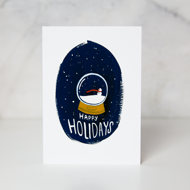Christmas card of a drawn snow globe with a snowman inside with the Happy Holidays wording underneath and a dark blue background called snow globe holidays by artist Lauren Suh