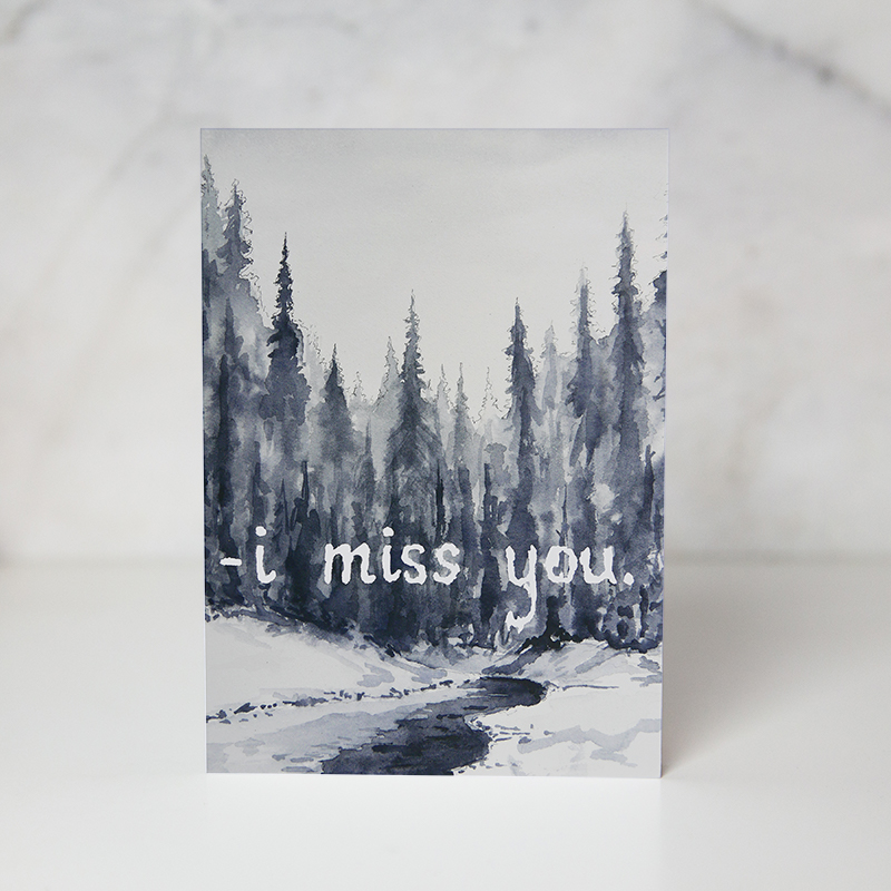 holiday card of a drawn snowed and iced river with giant tree in the background and the I miss you wording called miss you by artist Seth Spencer