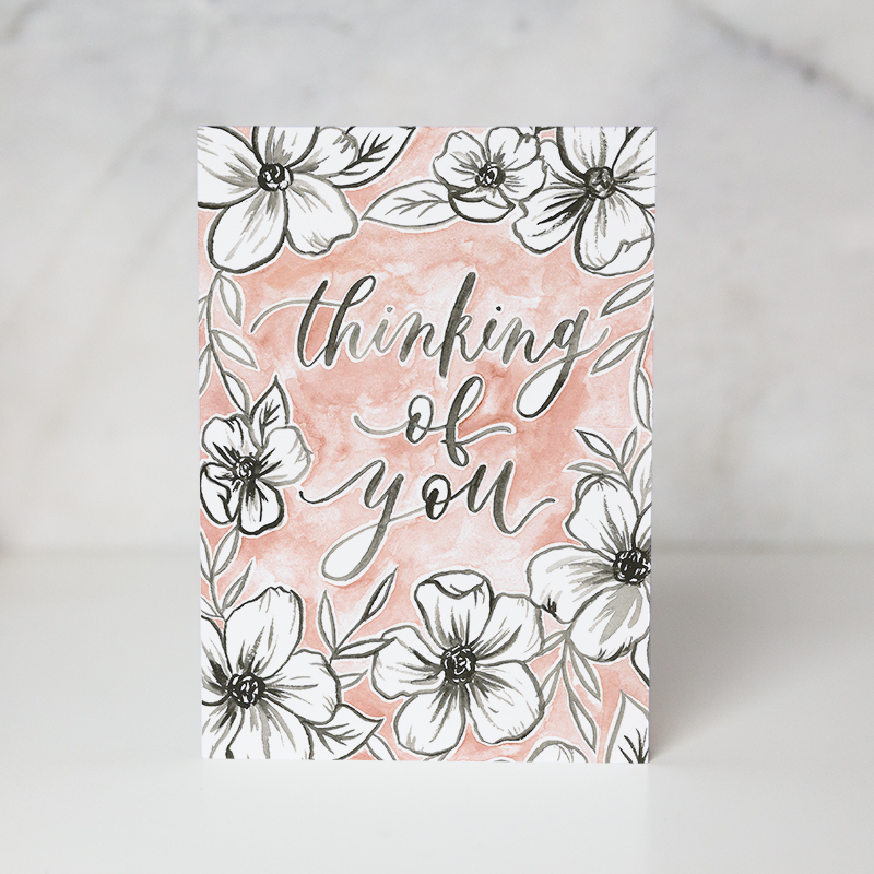 sympathy card with some black and white flowers in a pinkish colored background with the Thinking of you wording in the middle of the card called thinking of you by artist Jordan Marshall