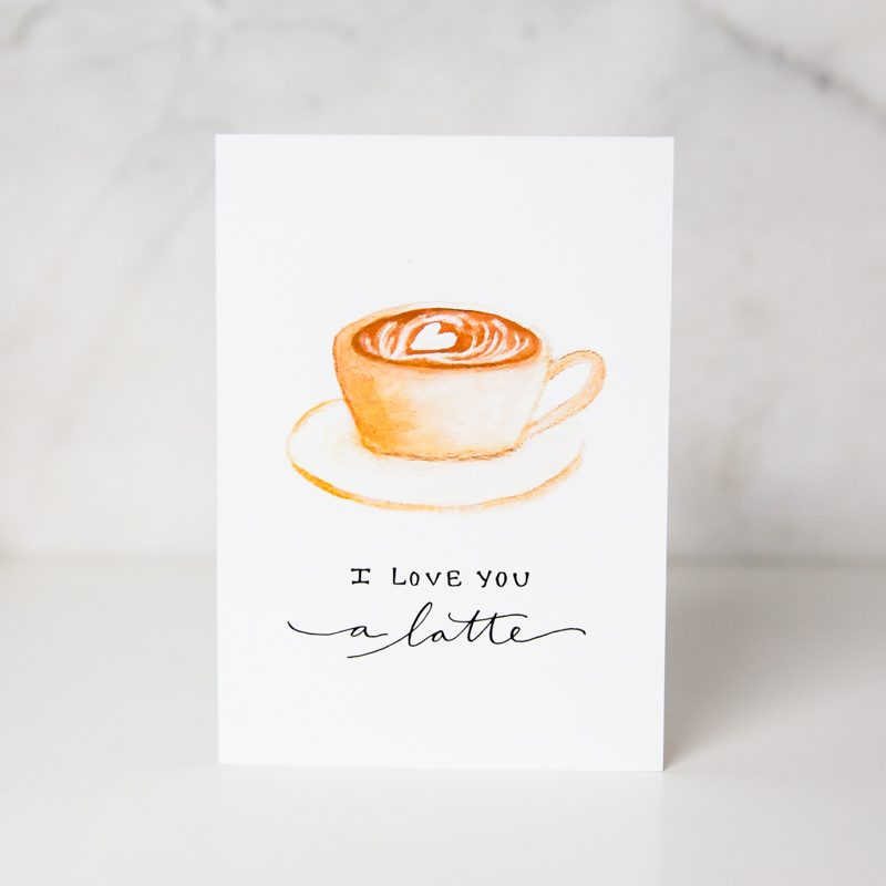 love card of a painted cup of coffee with a heart foam and the I love you a latte wording underneath in a complete white background called love you a latte by artist Sarah Brown