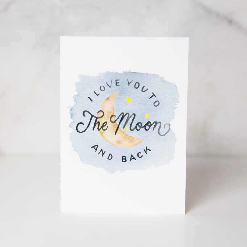 I love you to the moon and back card with a sky, stars and a moon drawn behind the wording called to the moon by artist Jordan Marshall