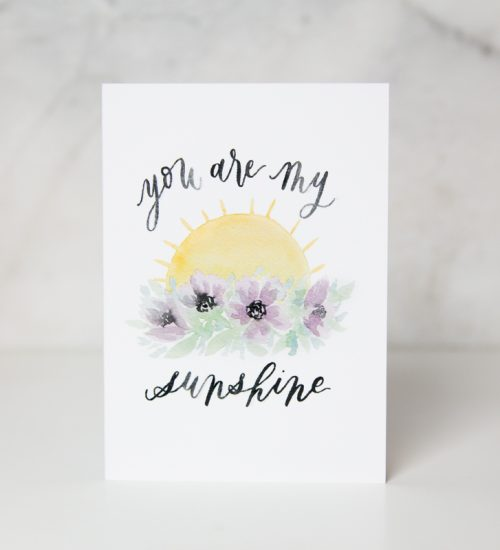 sympathy card of a painted sunset behind purple flowers with the You are my sunshine wording in a complete white background called sunshine by artist Jordan Marshall
